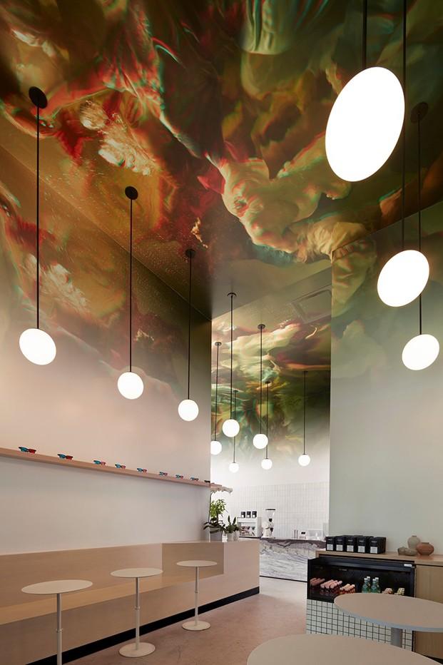 Sala interior local con vista al fondo de la barra y mobiliario de mesas circulares blancas y banco corrido en madera natural. Iluminación de bolas blancas con cordón negro pendientes del techo.