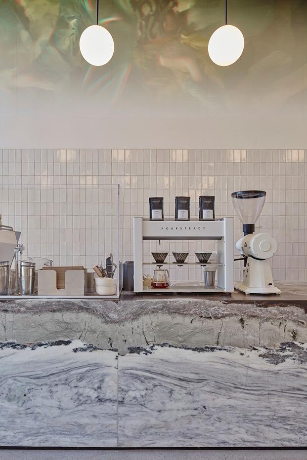 Backoffice de la barra con pared revestida en ceramica esmaltada en blanco brillo y detalle del mármol azul de la barra