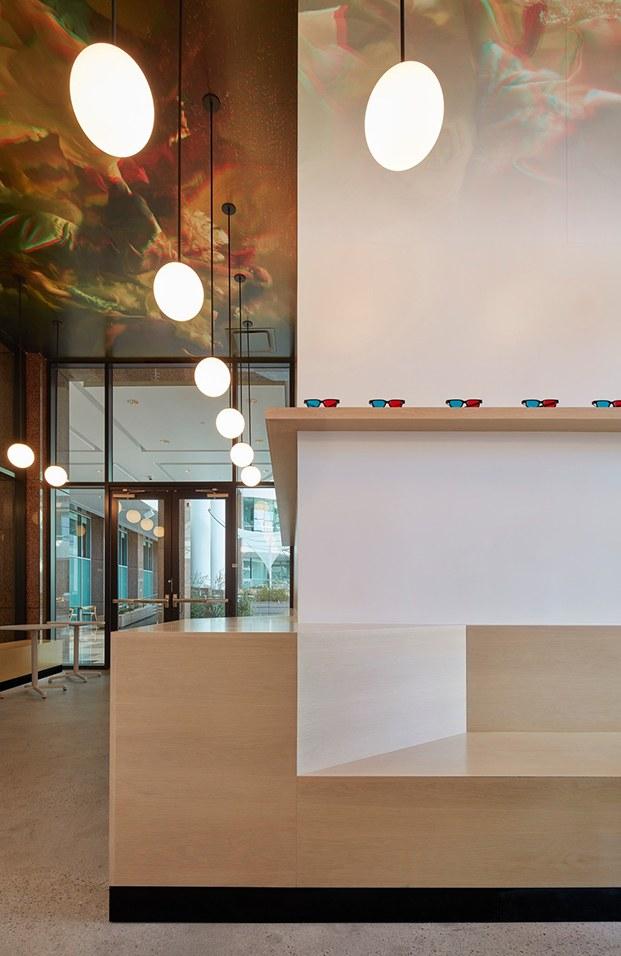 Detalle de la esquina del local con banco de madera natural y estante corrido con gafas visión 3d. Intervención en techo de vinilo con imagen 3d impresa.