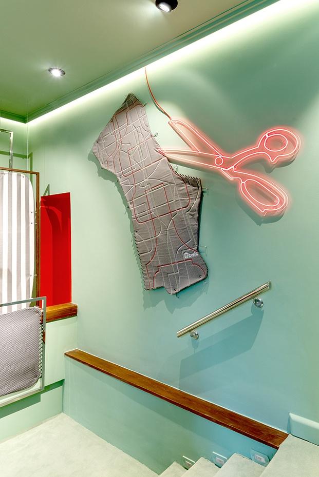 Un patrón XXL y unas tijeras rosas de neón iluminan la pared del esapacio de estudi{H}ac  para Sunbrella en Casa Decor 2020