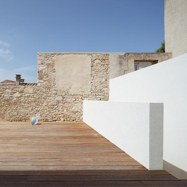 Composición abstracta exterior del patio con la contraposición de muros de piedra originales y muros blancos de la nueva intervención