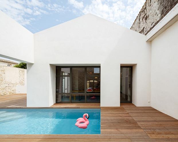 Patio descubierto con piscina y fachada blanca a dos aguas