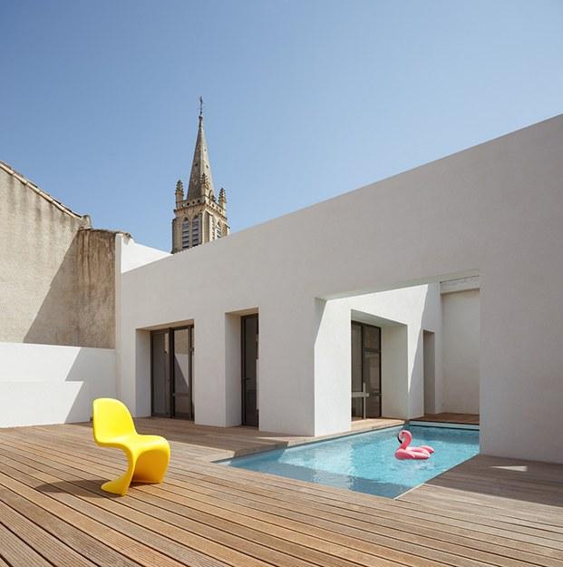 Vista exterior del patio y la piscina con los muro perimetrales blancos y el campanario de una iglesia al fondo
