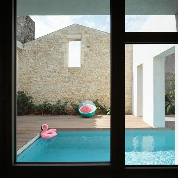 Vista del patio y la piscina desde el interior con carpinterías negras