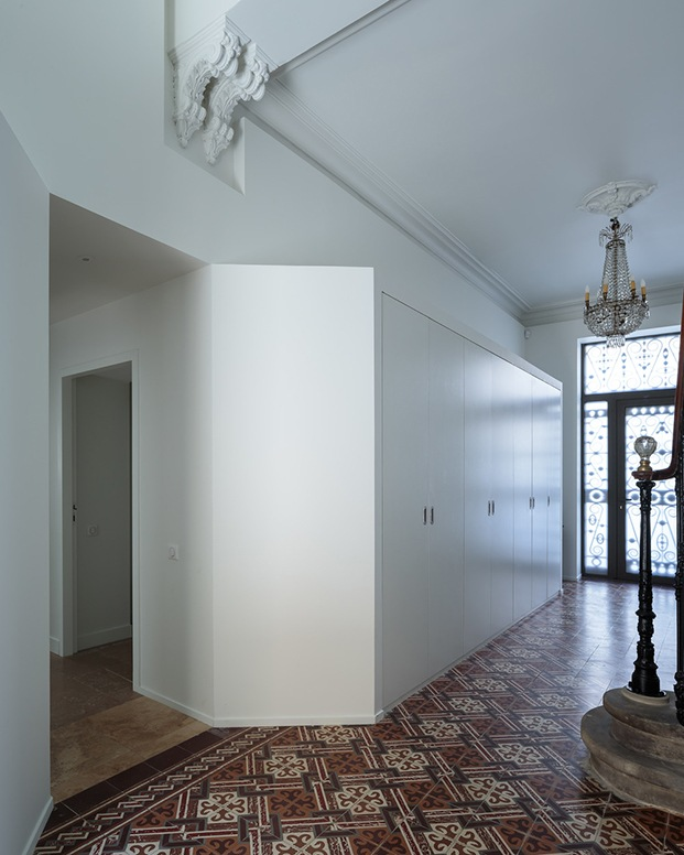 Vista interior de la entrada con un mueble de almacenamiento blanco integrado en la pared frente a la escalera