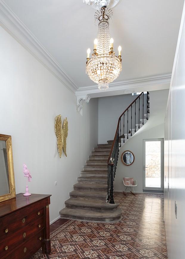 VIsta interior de la escalera de piedra  con barandilla negra y luminarias y mobiliario clásico