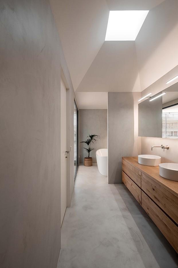 Vista del baño de la vivienda diseñada por Company Studio con mobiliario a medida y suelos de microcemento