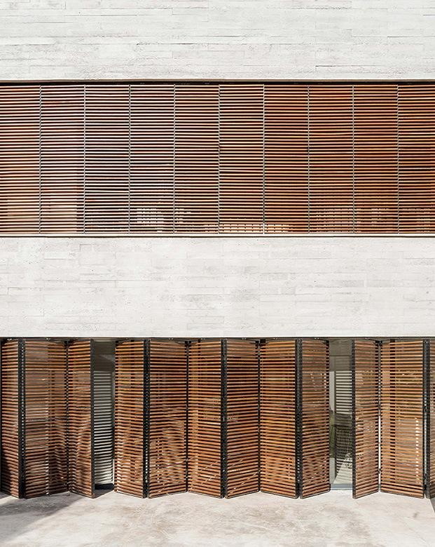 Unas persianas tipo acordeón diseño de Company Studio permiten aislar y separar los distintos espacios de la vivienda