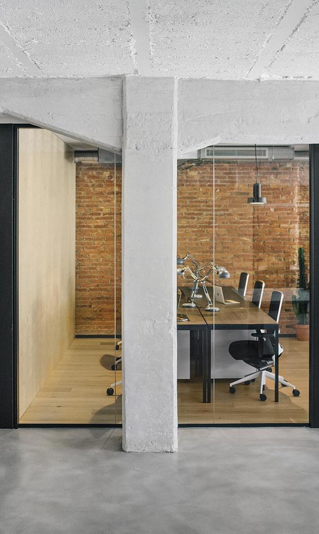 Vista desde un pasillo del interior de una oficina. En primer plano una columna de hormigón visto y por detrás carpintería metálica en negro conpaño de cristal. El interior de la oficina con suelo y pared de madera natural y pared del fondo de ladrillo visto. Mesa corrida con puestos de trabajo en madera muy oscura.