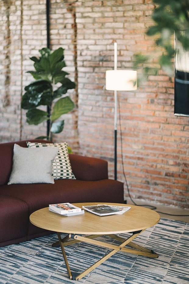 Primer plano de un rincón de los salones de las zonas comunes con lámpara tipo Milá, sofá en tonos granates, alfombra en azules y mesa auxiliar circular en madera natural con revistas encima.