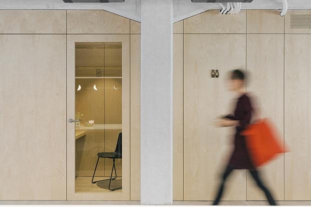 Vista desde el pasillo del panelado de madera de las salas de conferencia y núcleo de baños. En primer plano pilar y viga de hormigón visto.