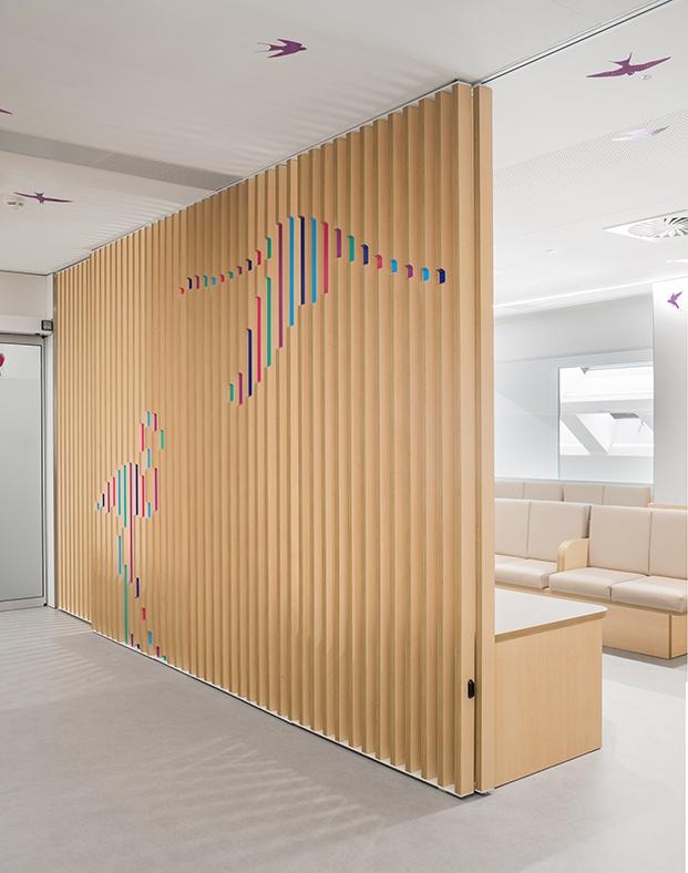 Celosía de madera natural que filtra las vistas de la sala de estar. Láminas de canto de madera con un rebaje pintado de colores y que en perspectiva generan las silueta de aves.