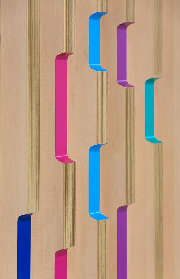 Detalle del rebaje en cada una de las lamas de madera contrachapada con el canto pintado en rosa, magenta, azul y verde agua.