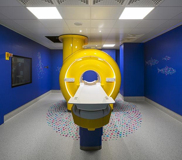 Vista interior de la sala de tac. La maquinaria es de color amarillo y las paredes de la sala en azul fondo marino con vinilos de siluetas de peces.
