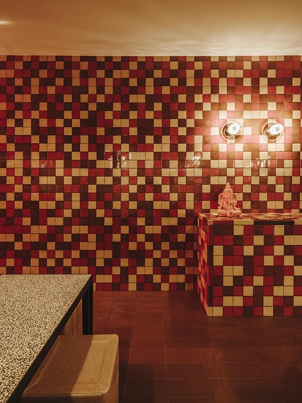 Las balsosas en tonos rojos naranjas y rojos en la pared juegan con el significado de Mirch, que es picante