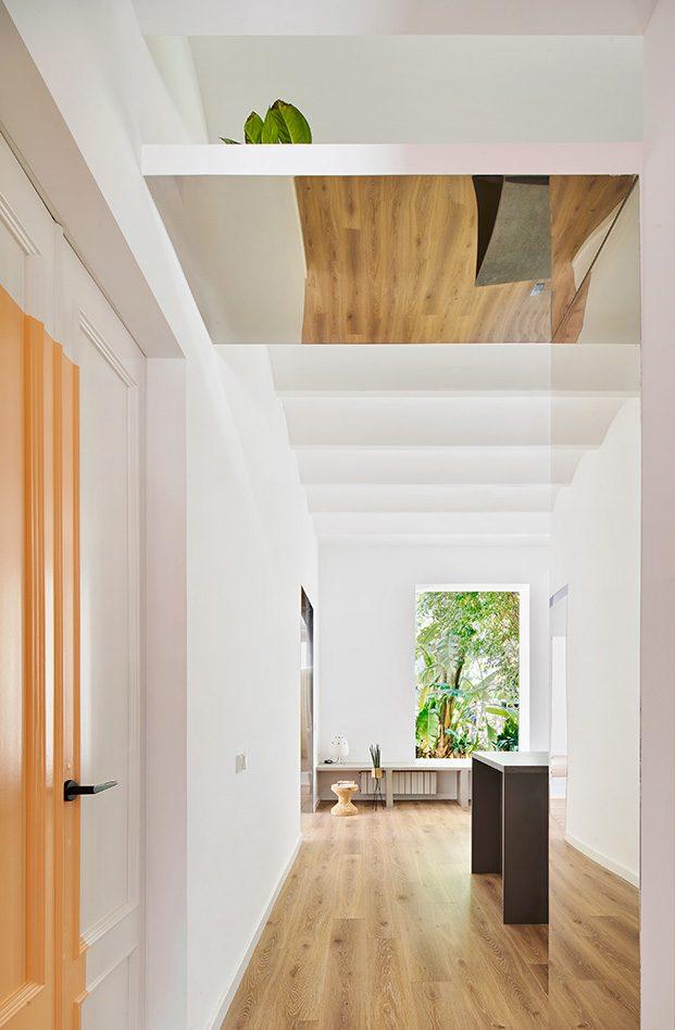 Desde la entrada se accede al espacio común del apartamento proyectado por Raúl Sánchez que acoge el salón, comedor y la cocina
