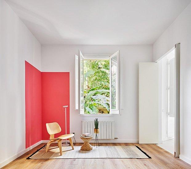 Uno de los rincones de estar abierto al jardín y con un toque de color fucsia. El uso del color es una de las señas de identidad del proyecto de Raúl Sánchez para este apartamento