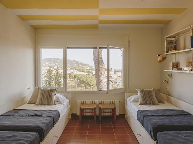 Para dar un aire nuevo a los dormitiorios de esta casa en la playa, Isabel López Vilalta ha creado toques de color en los techos
