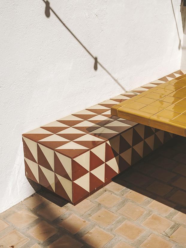 Detalle del banco y la mesa que ha diseñado Isabel López Vilalta para el comedor al aire de libre de esta casa de playa. Está hecho con la cerámica típica de la zona