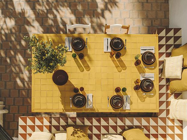 La cerámica artistica y popular de la zona revisten la mesa y el banco del comedor de verano
