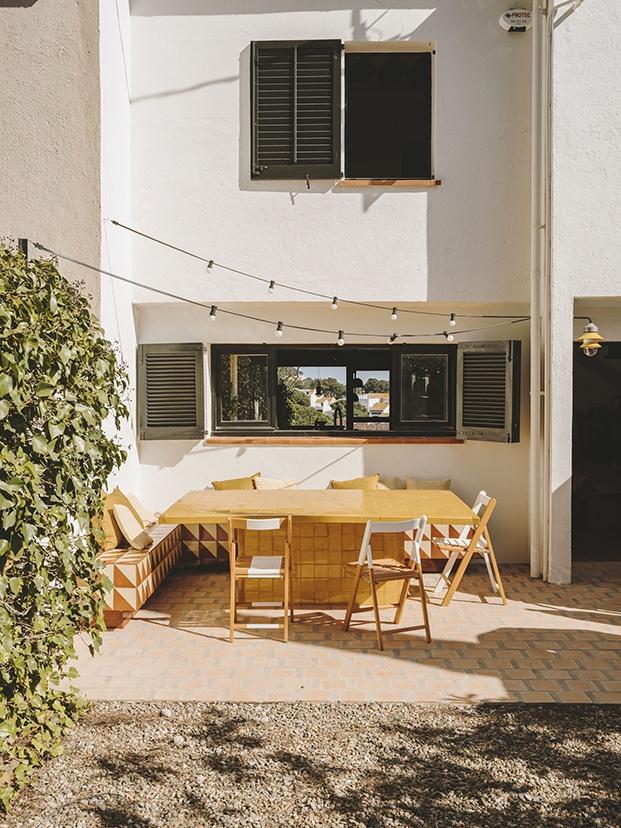 El comedor de verano cuenta con gran mesa  y un banco construidos en la cerámica esmaltada clásica de esta  zona