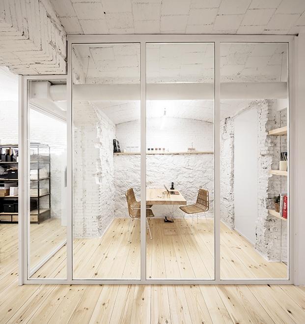 La zona de oficina, a la vista pero aislada con carpintería de perfiles blancos
