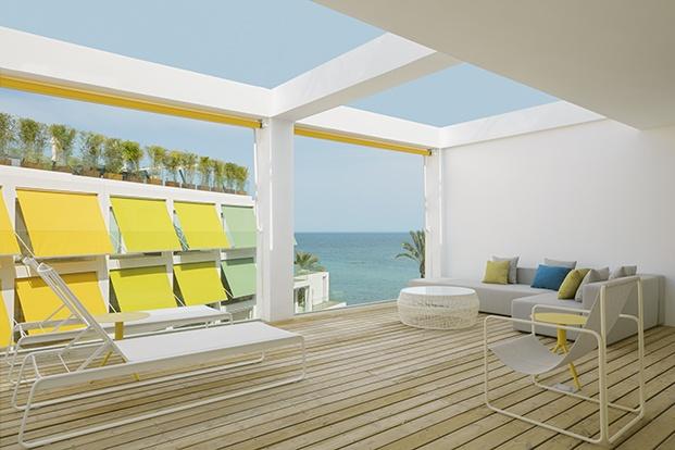 Una de las amplias terrazas con el azul del mar y el amarillo de los toldos como protagonistas