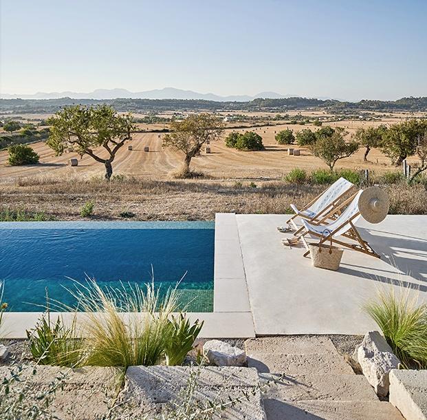 La piscina se encuentra sobre una superfice de hormigón en un nivel más bajo que la casa