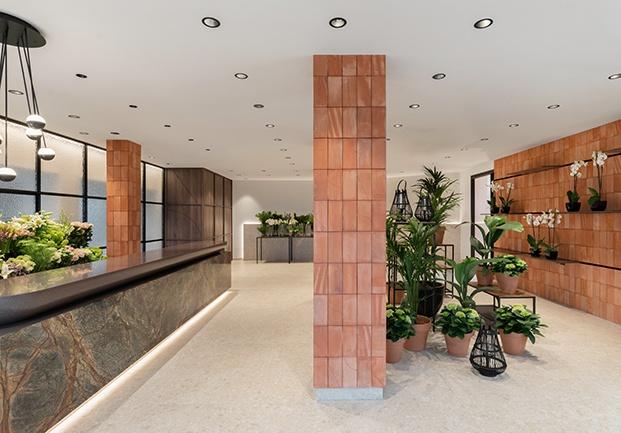 Vista general de la floristería RosanFlor. A un lado, el mostrador hecho a medida, al otro un muro de ladrillo para exponer plantas y flores