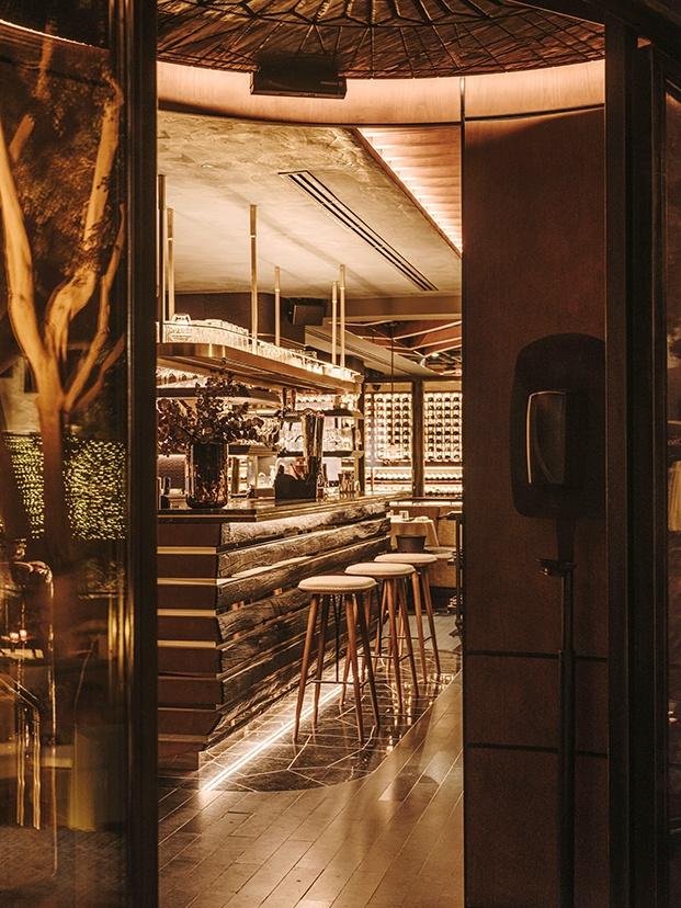 Entrada al restaurante Leña y vista de la barra y la bodega, al fondo