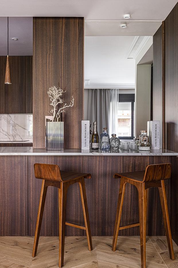 Vista de la barra de la cocina de este piso señorial madrileño. Se ha realizado a medida con madera de eucalipto y mármol