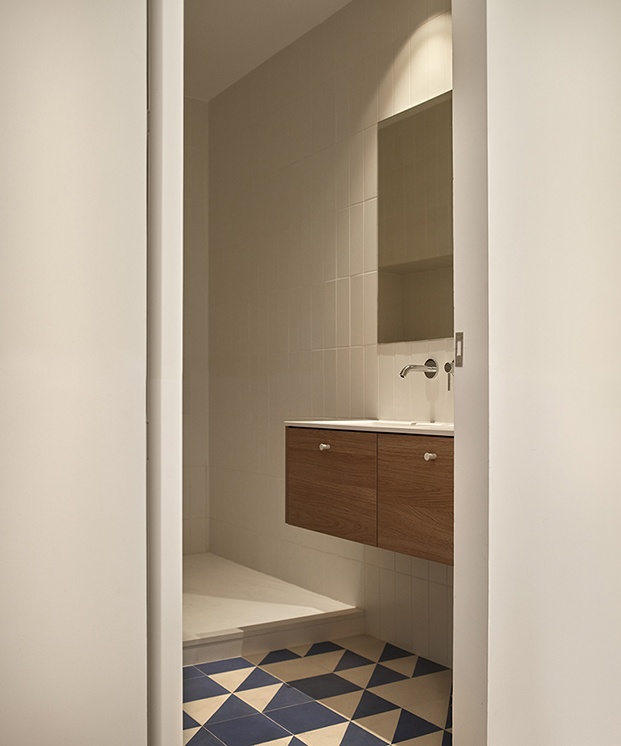 Vista del baño principal con lavabo suspendido y zona de ducha