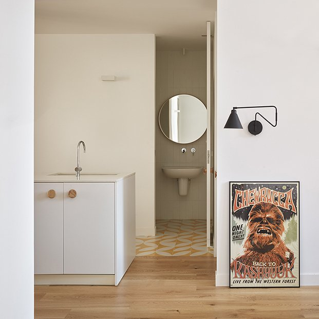 Uno de los carteles de cine de la pareja, la cocina y el baño de cortessía al fondo