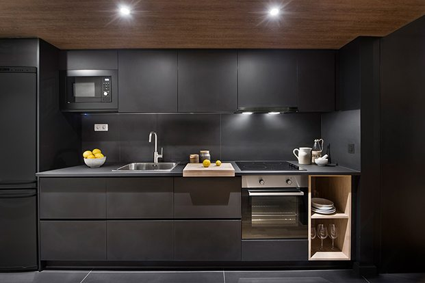 La cocina del ático en Barcelona, juega a romper los esterotipos de casa femenia y se ha creado en negra.