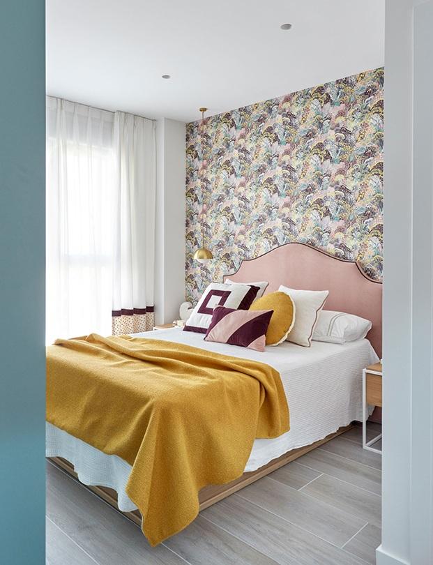 Tonos papeles y un papel pintado en la pared del cabecero personaliza el dormitorio