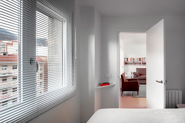 La vivienda principal con cortinas venecianas que tamizan el paisaje urbano cercano