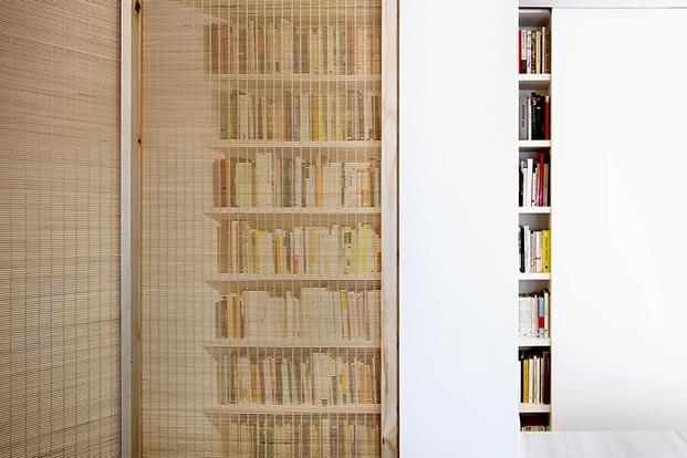 Una mampara tipo estor, y otra corredera camuflan parte de las librerías en la vivienda del escrlitor