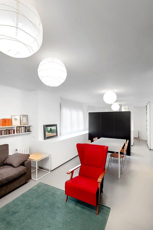 Un mueble negro separa las dos zonas de la casa, la estar y comedor de la de la zona de dormir
