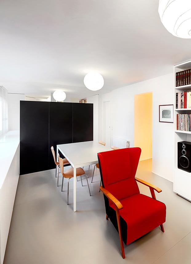El mueble negro pone fondo y contrapunto al blanco de la vivienda. Las sillas Jacobsen y la butaca provienen de la antigua vivienda del escritor