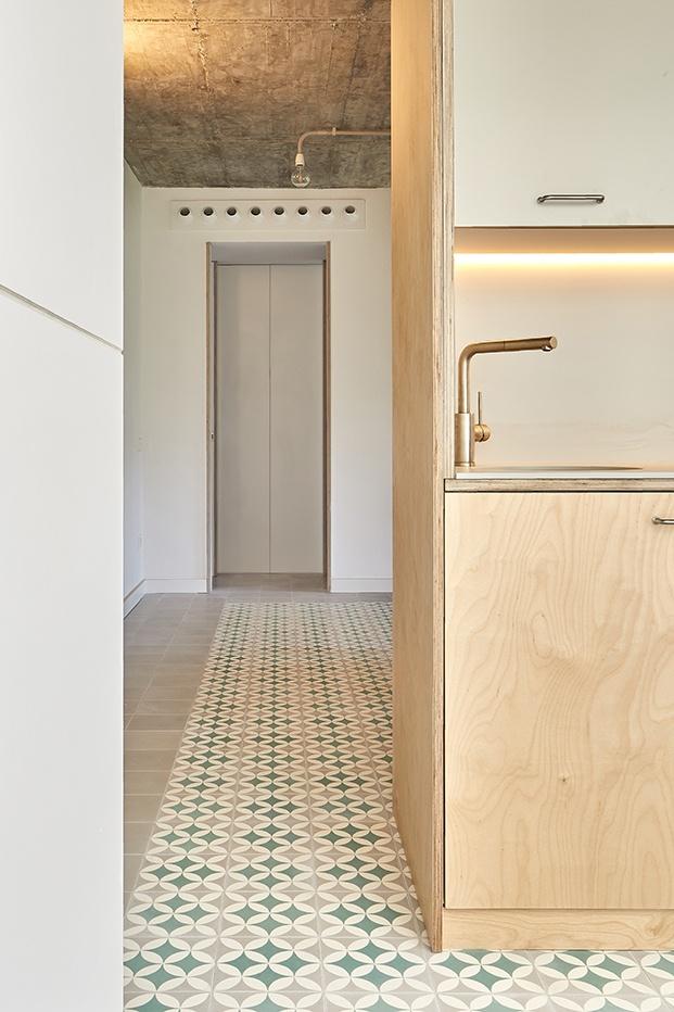 La cocina, en blanco y madera, inegrada en el ambiente