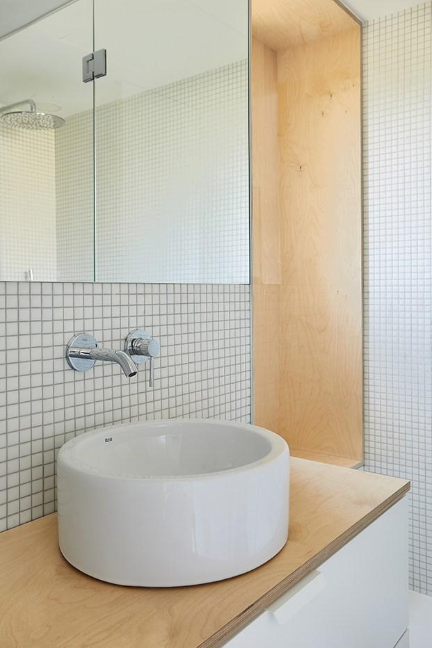 Cerámica y madera en el baño, con mobiliario blanco y lavamos sobrelavabo de Roca