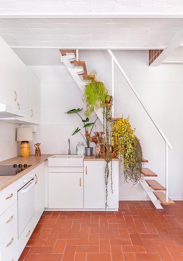 Detrás de la cocina, una escalera conduce a la planta alta que acoge el dormitorio principal, una sala de estar y el baño