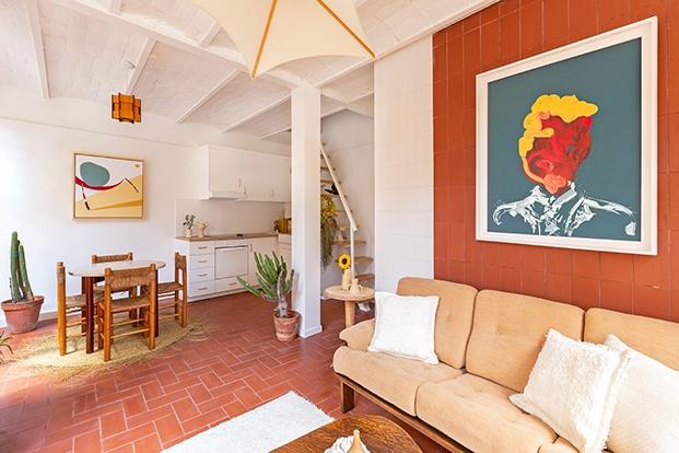 En el salón destaca el sofá AG Barcelona años 70, aterciopelado y en un tono marrón muy suave, con varios cojines marroquíes de lana