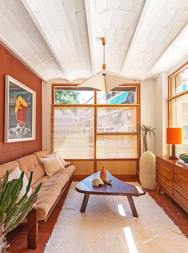 En el salón, piezas de mobiliario icónico y grandes ventanales, Unas   persianas de madera tamizan la luz