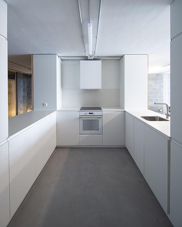 Vista de la cocina, en U, práctica y hecha a media con muebles blancos por Garmendia Arquitectos para esta vivienda de Bilbao