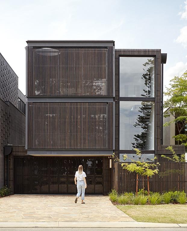Vista de la fachada de Shutter House con la segunda piel de listones de madera cerrada