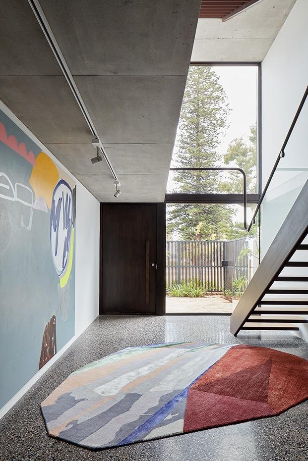 Arte en las paredes y arte en el suelo, en la entrada.  una espectacular alfombra de Patricia Urquiola, la Fordite de CC Tapis, preside el hall
