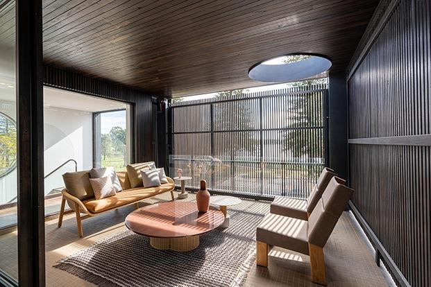 Vista de una de las zonas blacón  iluminada con el claroscuro de la persiana de la fachada y decorada con muebles de Patricia Urquiola para Kettal colecciones Vimini y Kettal