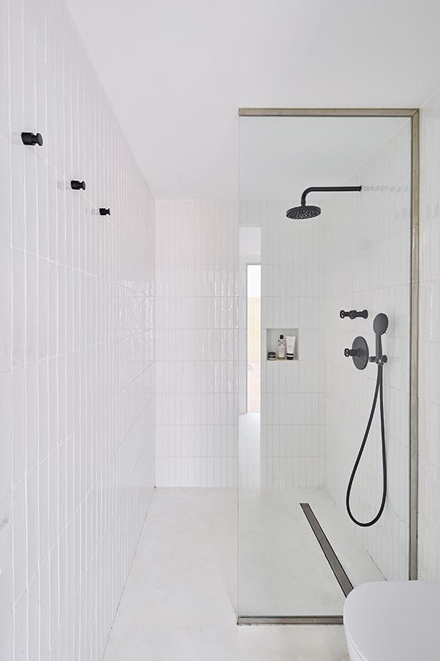la zona del ducha completamete revestida en cerámica blanca