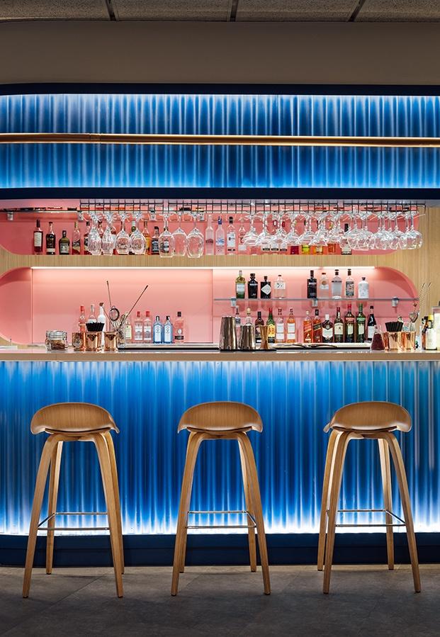 Vista del bar retroiluminado y decorado con el taburete 3D
